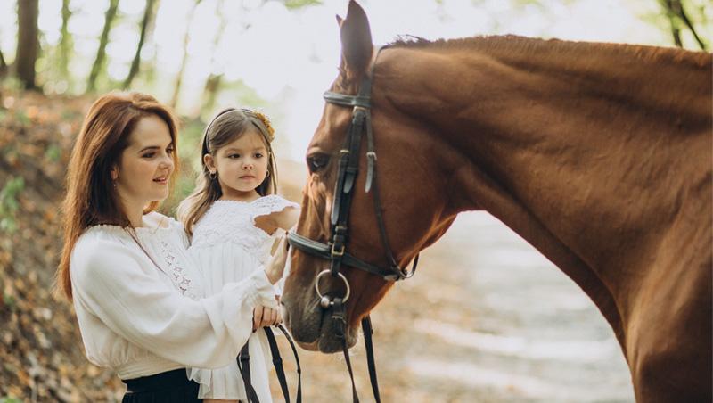 Matka z córką głaszczą konia